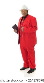 Full-length image of a senior man happily holding his Bible while wearing a red 3-piece suit and white fedora.  On a white background.
