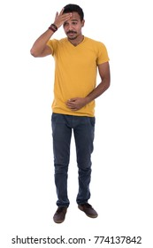 Full-length image of sick man having a headache and stomach. He is wearing a yellow t-shirt, blue trousers, shoes, and bracelet. Isolated on white background.