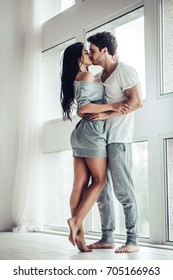 Full-length image of young beautiful couple is enjoying the company of each other at home. Hugging and kissing.