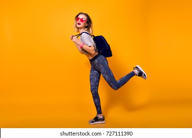 Full-length indoor portrait of girl wearing leggings, running on yellow background. Pretty slim female model in sneakers with backpack fooling around in studio.