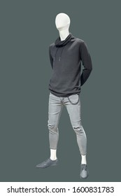 Full-length male mannequin dressed in black sweater and gray jeans, isolated. No brand names or copyright objects.