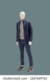 Full-length male mannequin dressed in blue jacket and jeans over green background. No brand names or copyright objects.