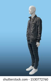 Full-length male mannequin dressed in fashionable clothes, isolated on blue background. No brand names or copyright objects.
