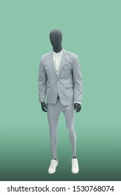 Full-length male mannequin dressed in gray suit, isolated. No brand names or copyright objects.