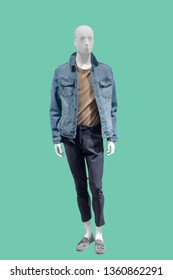 Full-length male mannequin dressed in jeans jacket and black trousers, isolated on green background. No brand names or copyright objects.