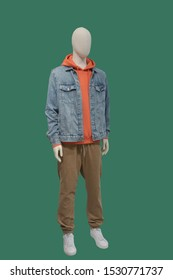 Full-length male mannequin dressed in warm casual clothes, isolated on green background. No brand names or copyright objects.