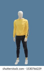 Full-length male mannequin dressed in yellow sweater and black jeans, isolated on blue background. No brand names or copyright objects.
