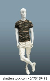 Full-length male mannequin in summer casual clothes, isolated on gray background. No brand names or copyright objects.