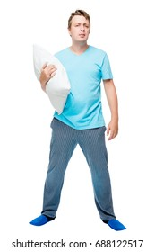 Full-length man in pajamas with pillow on white background