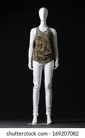 db7b628e34329 full-length mannequin female dressed in shirt and white trousers on black  background