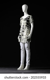 full-length mannequin female in white shirt and white jeans on black background