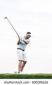 Full-length of mid-adult man swinging golf club against clear sky