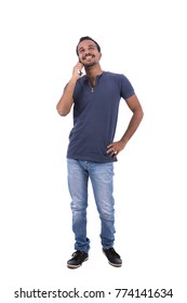 Full-length photo of adult man wearing a denim t-shirt, light blue jeans pants and sneakers is talking on mobile phone. Isolated on white background.