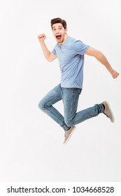 Full-length photo of funny man 30s in casual t-shirt and jeans running or jumping in air isolated over white background