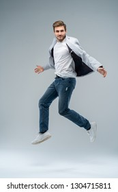 Full-length photo of funny man in casual t-shirt, blazer and jeans running or jumping in air isolated over gray background