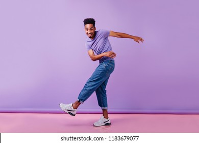 Full-length photo of glad african man dancing with sincere smile. Male model in jeans and purple t-shirt having fun.