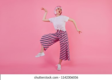 Full-length photo of joyful girl in peruke fooling around during studio photoshoot. Magnificent funny lady in periwig dancing on pink background.