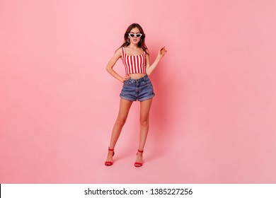 Full-length photo of long-legged girl in red sandals with heels, denim shorts and cropped top on a pink background