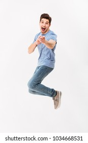 Full-length photo of positive man in casual t-shirt and jeans jumping and pointing finger on camera, isolated over white background