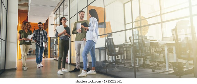 Full-length photo of positive young coworkers in office building