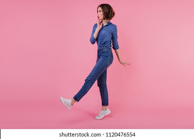 Full-length photo of shapely glad girl in white sneakers. Slim debonair young woman in jeans posing on pastel background.