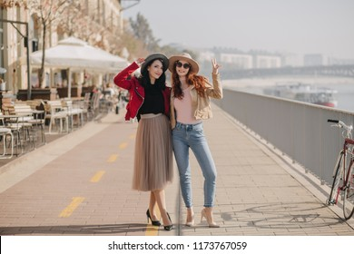 Full-length photo of slim ginger girl in casual clothes spending weekend with friend. Adorable brunette woman in long skirt standing with sister at embankment.