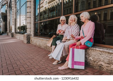 Full-length photo of three adult women discussing new purchases while holding shopping bags. Copy space in left side