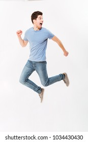 Full-length photo of uptight scared man 30s in casual t-shirt and jeans running away in studio isolated over white background