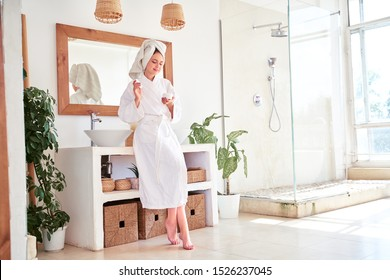 Full-length photo of woman in bathrobe with cream in her hands in bathroom.