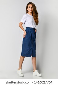 Full-length photo of a young brunette girl with long hair in a white blouse and blue skirt. on a light background.