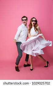 Full-length photo of young fashion couple in trendy stylish clothing dancing and having fun isolated over pink background