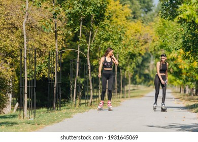 Full-length picture of sexy sportswomen rollerskating in the park