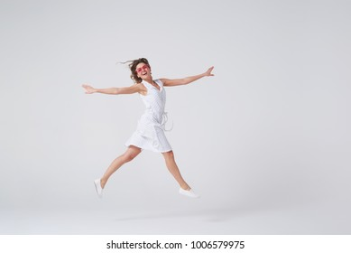 Full-length of playful girl gesturing and smiling while jumping against background