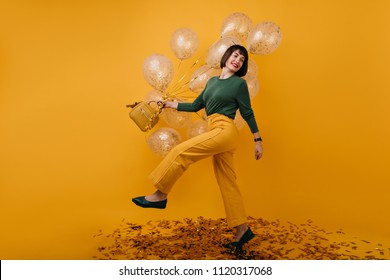 Full-length portrait of adorable woman dancing in studio with party balloons. Indoor shot of blissful brunette girl in yellow pants having fun in her birthday.