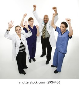 Full-length portrait of African-American man and Caucasian women medical healthcare workers in uniforms cheering with arms raised standing against white background.