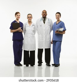 Full-length portrait of African-American man and Caucasian women medical healthcare workers smiling in uniforms standing against white background.