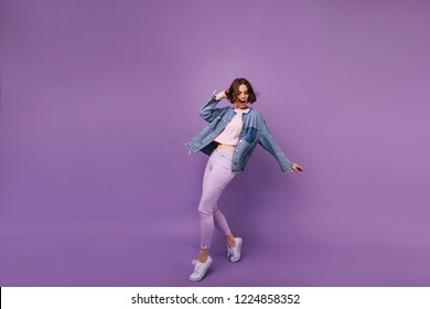 Full-length portrait of attractive slim girl wears white sport shoes. Indoor photo of enchanting caucasian woman dancing on violet background.