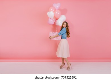 Full-length portrait of attractive stylish girl with gift wearing high heel shoes and midi skirt for friend's birthday party. Adorable curly young woman holding present box with balloons for event