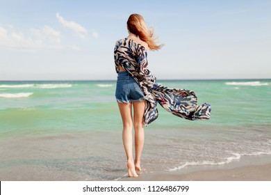 Full-length portrait from back of pretty slim  tan girl  enjoying horizon view at ocean resort.  Holiday and travel concept. Windy hairs. Blue ocean . California.
