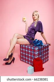 full-length portrait of beautiful blonde party girl siiting on large birthday gift box on pink