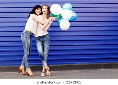 Full-length portrait of a beautiful mother with her daughter wearing blank white t-shirt and jeans posing against blue wall, minimalist street fashion style, family same look, sale concept.