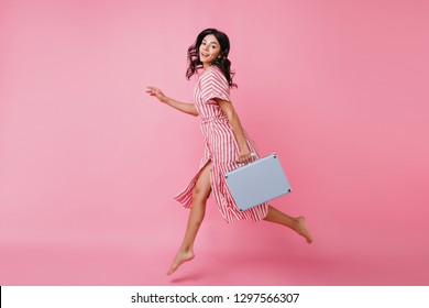 Full-length portrait of beautiful woman in jump on pink isolated background. Lady in striped outfit is moving fast with luggage