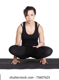 full-length portrait of beautiful woman working out yoga excercise padmasana (lotus pose) on fitness mat