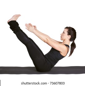 full-length portrait of beautiful woman working out yoga excercise paripurna navasana (full boat pose) on fitness mat
