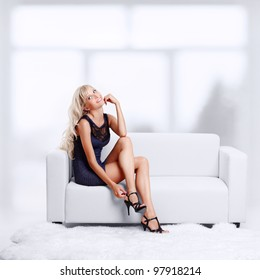 full-length portrait of beautiful young blond woman on couch checking court shoe fastener