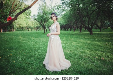 full-length portrait of the bride in a glamorous wedding dress outdoors