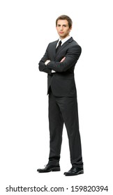 Full-length portrait of businessman with hands crossed, isolated on white background. Concept of leadership and success