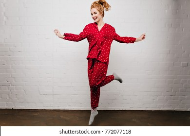 Full-length portrait of carefree caucasian girl dancing in red pajamas on light background. Gorgeous young woman in cute sleepwear jumping with smile.