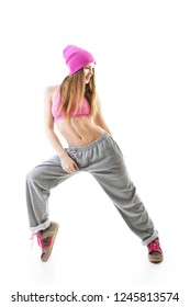 Full-length portrait of carefree girl in gray pants, pink top and hat jumping and dancing. Teen girl hip-hop dancer, over white background.