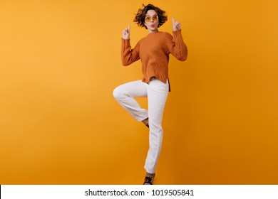 Full-length portrait of carefree girl in white pants jumping on orange background. Romantic lady with wavy hair dancing in knitted sweater.